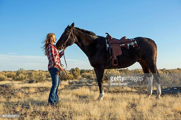 Caucasian woman standing with horse in field