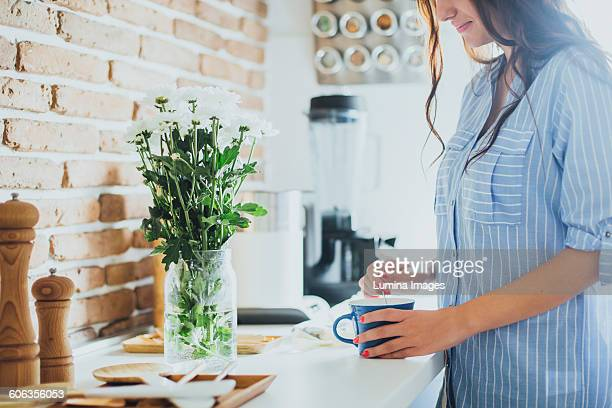 Caucasian woman stirring coffee in kitchen