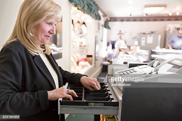 caucasian woman store owner takes money from the cash register - jeweller stock pictures, royalty-free photos & images