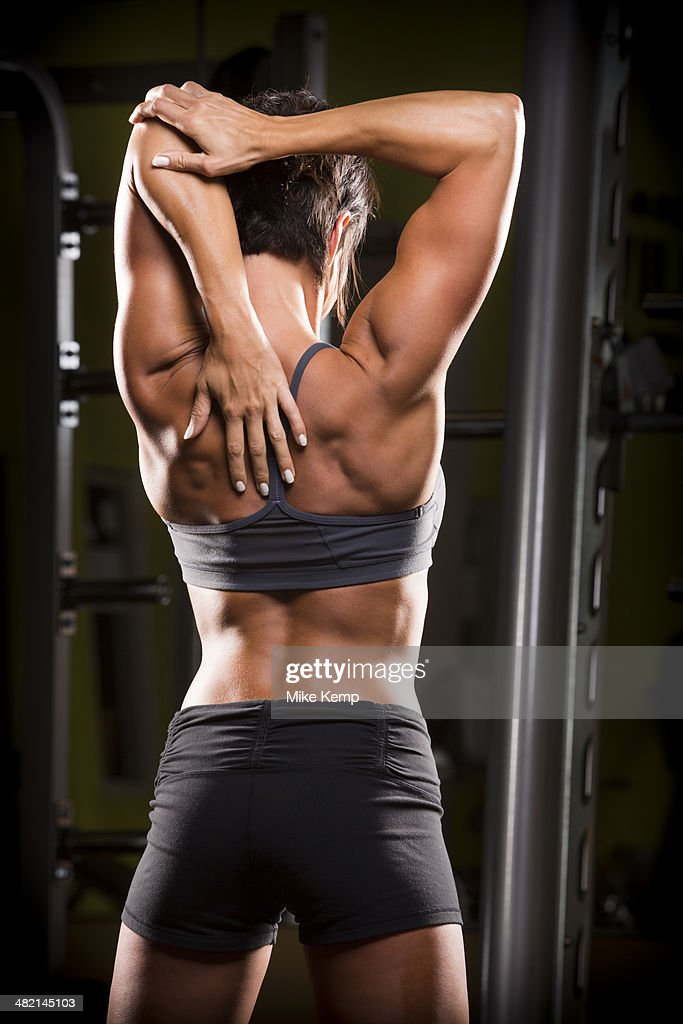 Caucasian woman stretching arm behind back in gym : Stock Photo