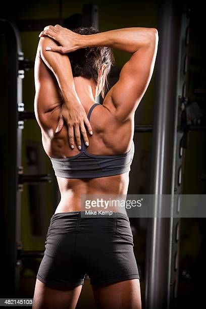 Caucasian woman stretching arm behind back in gym
