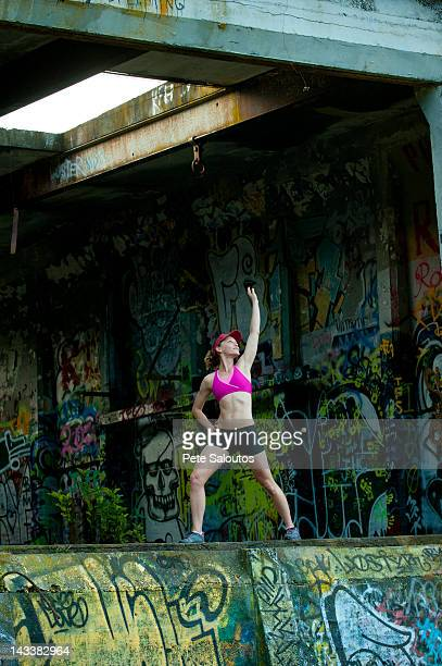 caucasian woman stretching in abandoned loading dock - pete vandal stock pictures, royalty-free photos & images
