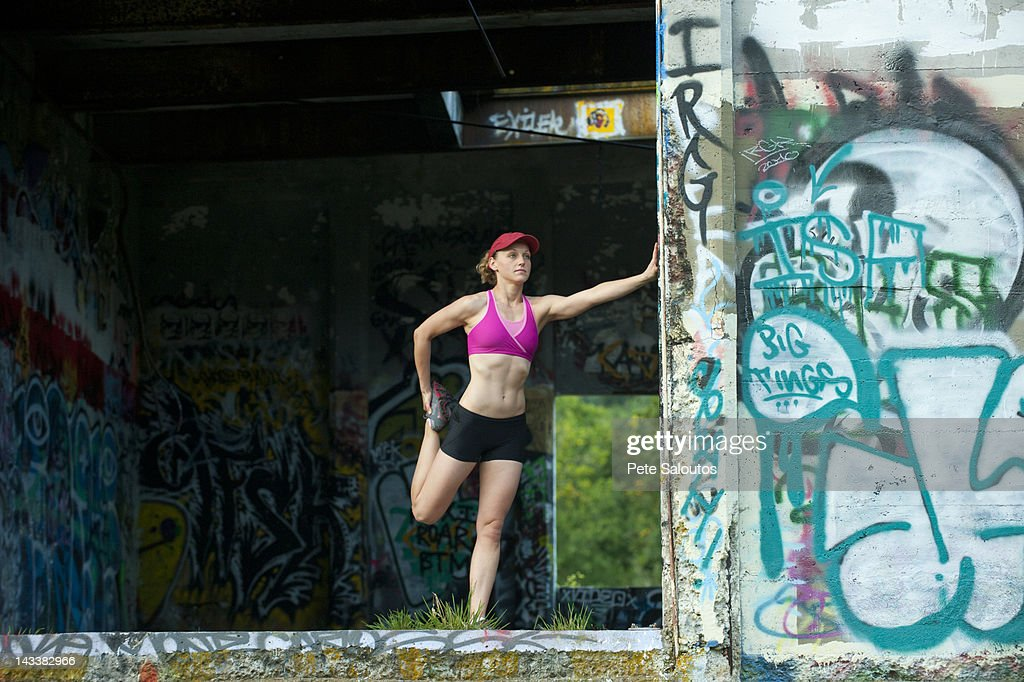 Caucasian woman stretching in abandoned loading dock : Stock Photo