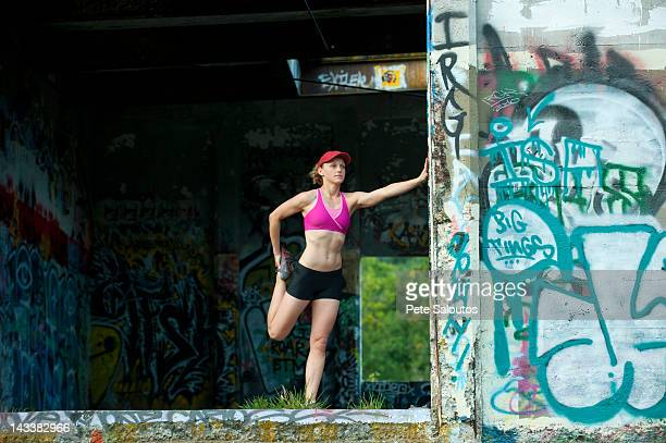Caucasian woman stretching in abandoned loading dock