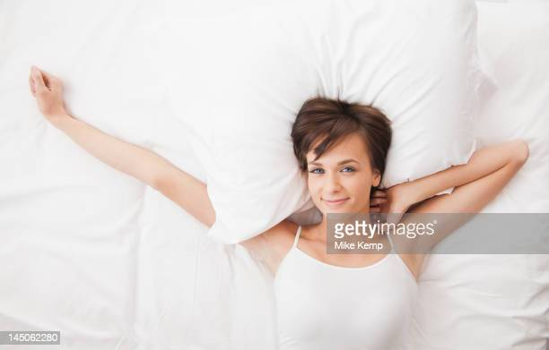Caucasian woman stretching in bed