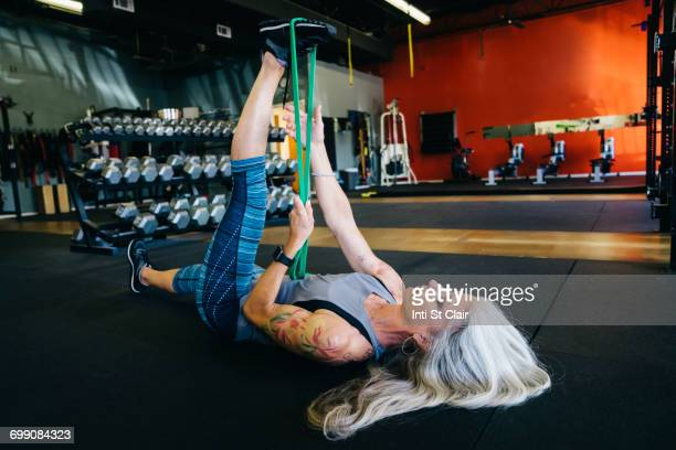 Caucasian woman stretching leg with resistance band