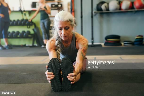 Caucasian woman stretching legs on gymnasium floor