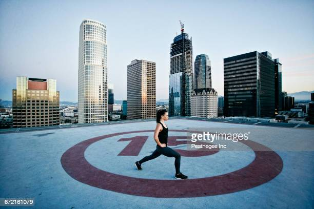 Caucasian woman stretching legs on urban rooftop