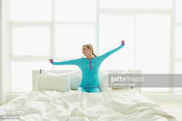 Caucasian woman stretching on bed