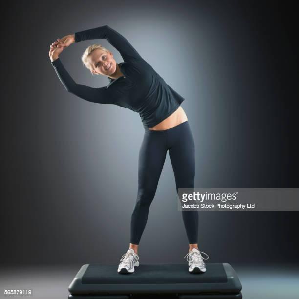 Caucasian woman stretching on platform