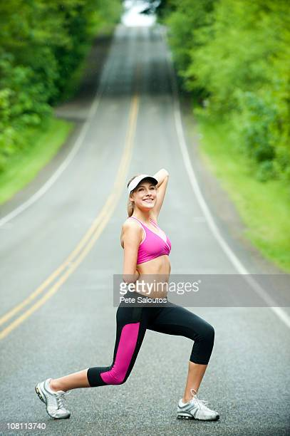 Caucasian woman stretching on remote road
