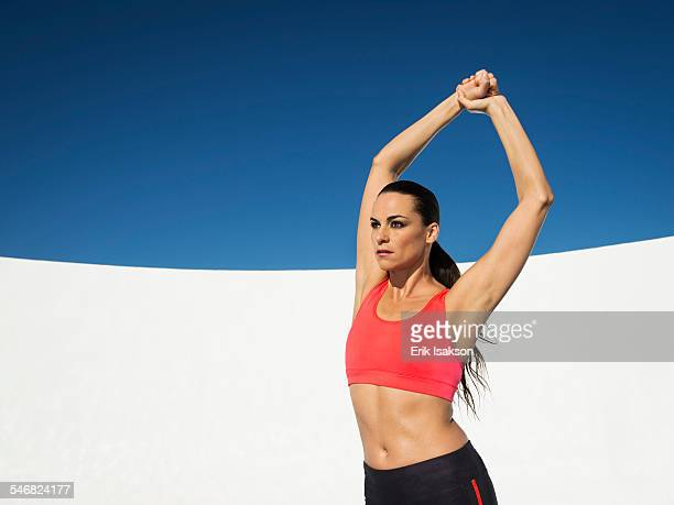 Caucasian woman stretching under blue sky