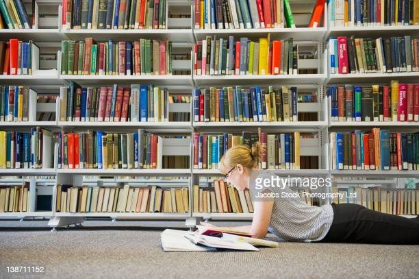 caucasian woman studying on floor of library - western australia stock photos and pictures