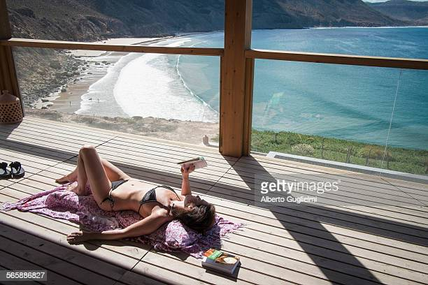 Caucasian woman sunbathing and reading book on deck over beach