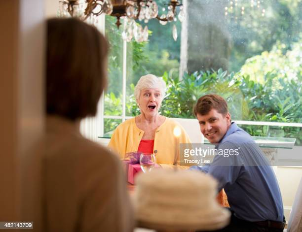 caucasian woman surprising mother with birthday cake - mother in law stock pictures, royalty-free photos & images