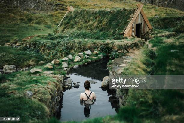 caucasian woman swimming in pond near rural house - stagno acqua stagnante foto e immagini stock