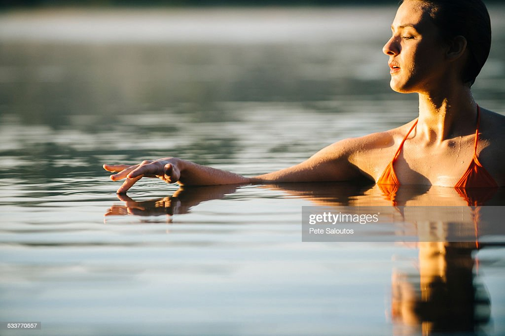 Caucasian woman swimming in still lake : Foto stock