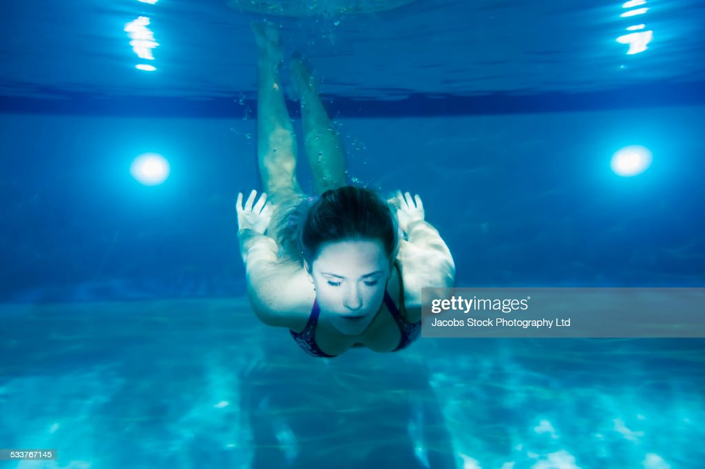 Caucasian woman swimming underwater in pool : Foto stock