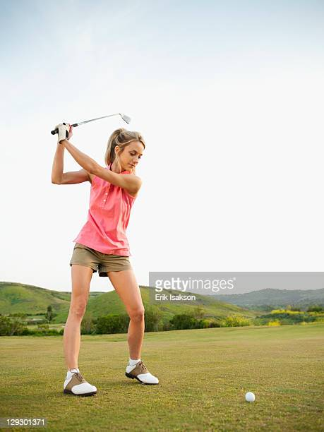 Caucasian woman swinging golf club on golf course
