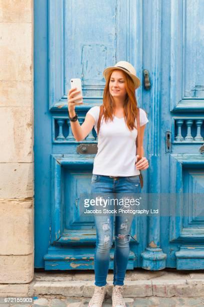 Caucasian woman taking cell phone selfie near blue doors