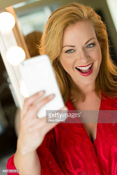 caucasian woman taking cell phone selfie - risque woman stock photos and pictures