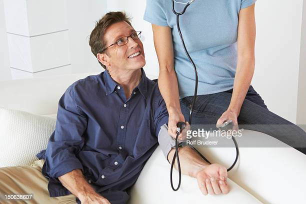 Caucasian woman taking husband's blood pressure