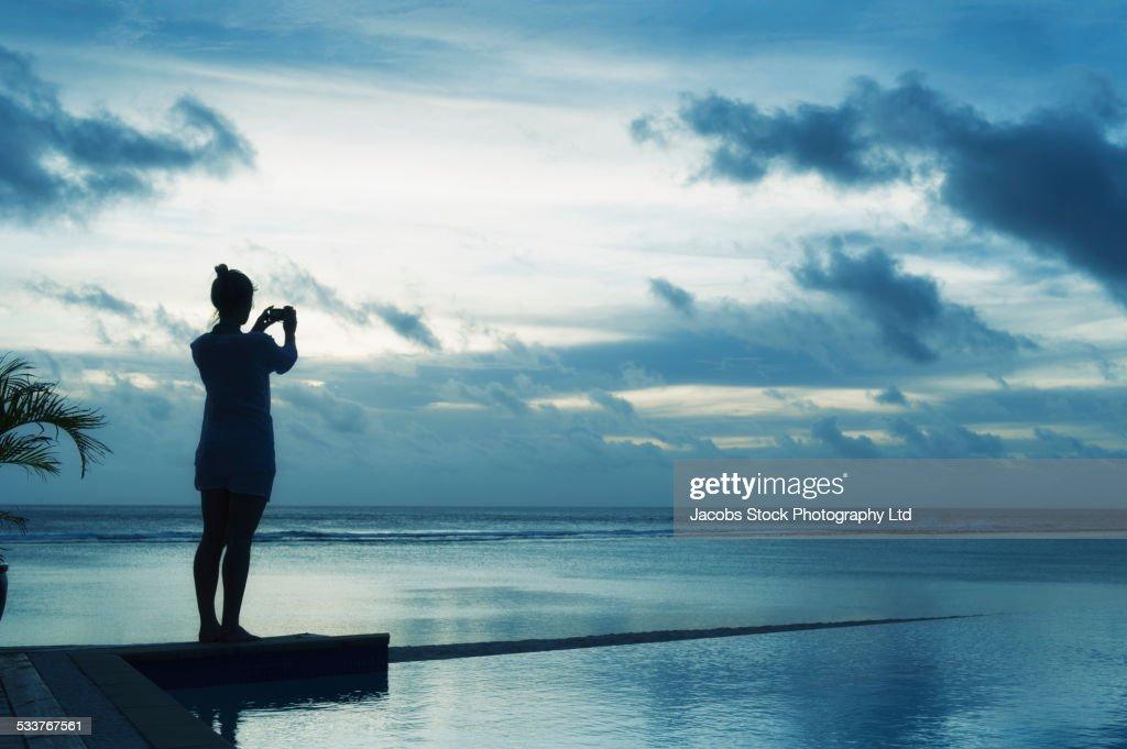 Caucasian woman taking photograph of sunset near swimming pool : Foto stock