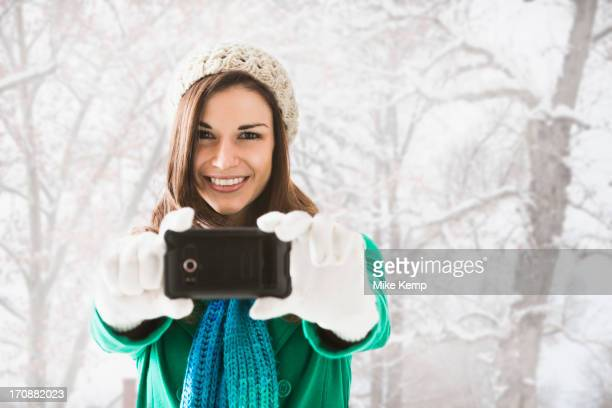 Caucasian woman taking pictures in snow