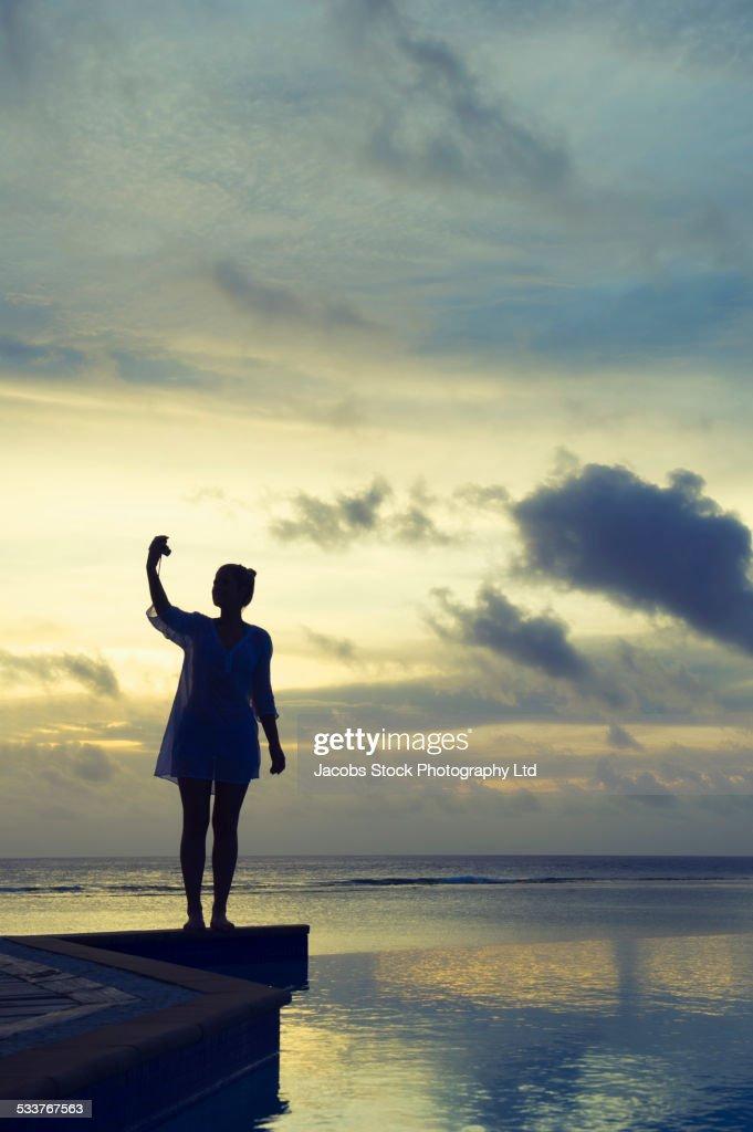 Caucasian woman taking selfie at sunset near swimming pool : Foto stock