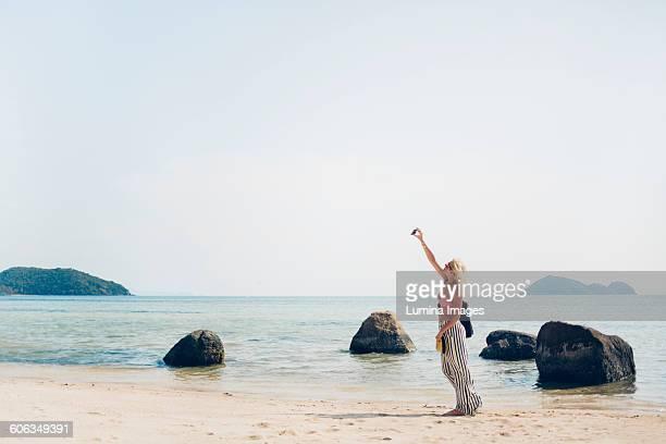 Caucasian woman taking selfie on beach