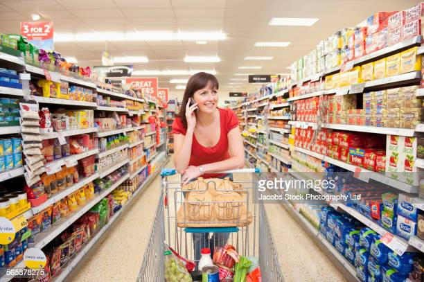 Caucasian woman talking on cell phone in grocery store