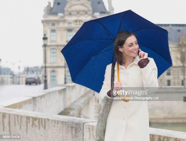 Caucasian woman talking on cell phone under umbrella on urban bridge