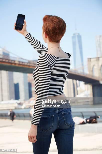 Caucasian woman talking selfie at waterfront