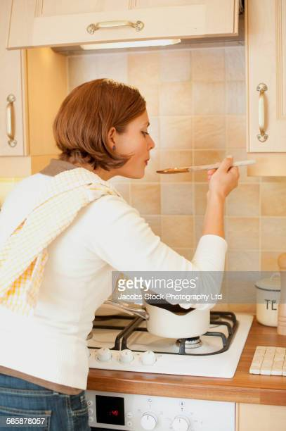 caucasian woman tasting food and cooking in kitchen - spalding england stock photos and pictures