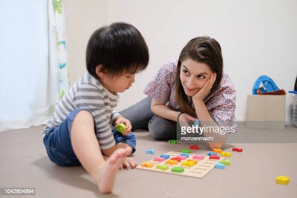 caucasian woman teaching english to asian toddler with alphabet blocks - english language stock pictures, royalty-free photos & images