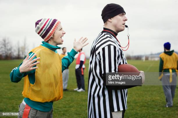 Caucasian woman team member arguing with a referee while playing non-contact flag football.