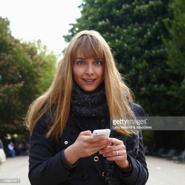 caucasian woman text messaging on cell phone - westeuropa stock-fotos und bilder