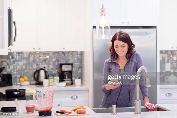 Caucasian woman texting on cell phone in domestic kitchen