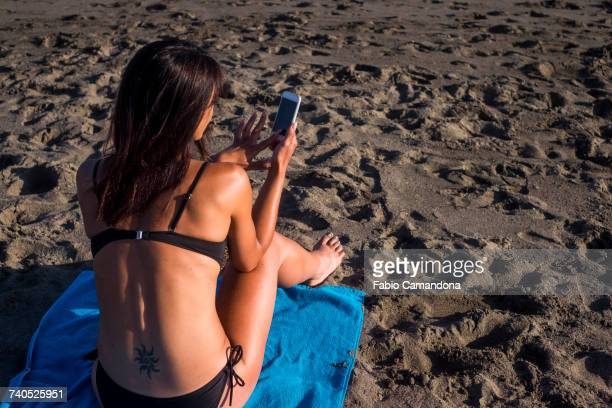 caucasian woman texting on cell phone on beach - lower back stock pictures, royalty-free photos & images