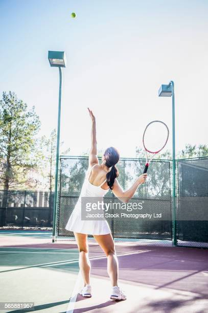 Caucasian woman throwing and serving tennis ball