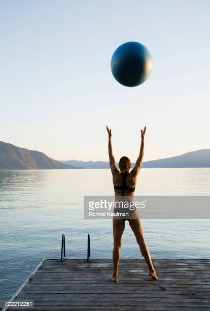 Caucasian woman throwing blue ball on dock at lake