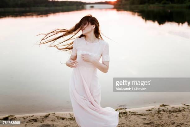 Caucasian woman tossing hair on beach