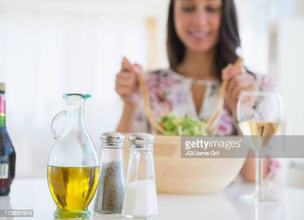 Caucasian woman tossing salad at lunch