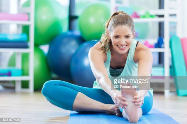 Caucasian woman touches toes during floor exercise