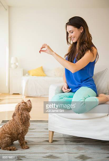 Caucasian woman training pet dog in living room