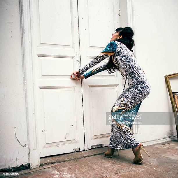Caucasian woman trying to open locked door