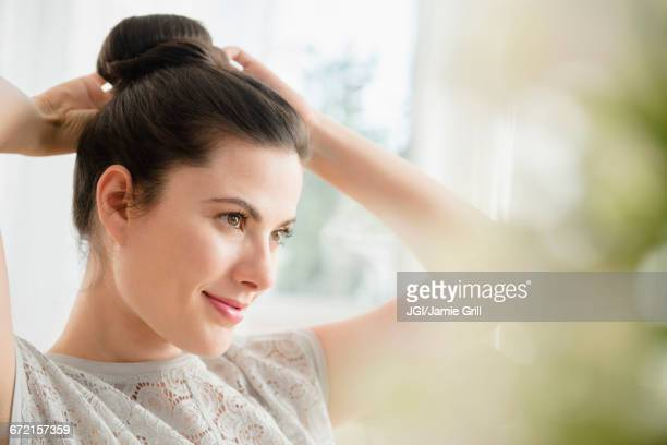 Caucasian woman tying hair in bun
