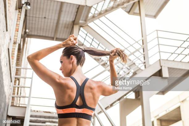 caucasian woman tying hair in ponytail - ponytail stock pictures, royalty-free photos & images