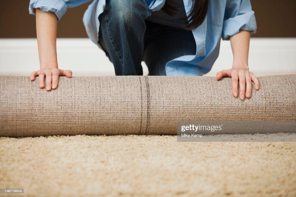 Caucasian woman unrolling carpet : Stock Photo