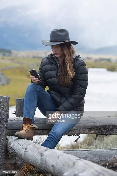 Caucasian woman using cell phone at rural river